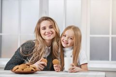 Older and younger sisters eating cookies and smile. Close up of two smiling sisters-younger and oder. Both girls have blonde straight hair. They are eating royalty free stock images