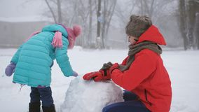Older and younger sisters with fun make a snowman in the street. Two sisters outdoors in the winter make a snowman stock video footage