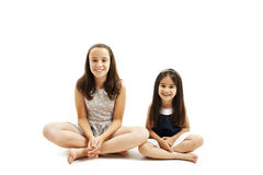 Older and younger sisters sitting on the floor Stock Images