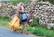 Olderly妇女运载在驴的黄色袋子 图库摄影