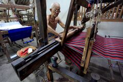 Oldest worker carefully checks the woven fabric