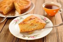 Oldfashioned apple pie with tea in orange cup Royalty Free Stock Images