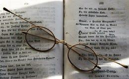 Oldfashioned exponeringsglas med en bok Royaltyfri Fotografi