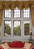 Oldfashioned window with drapes. Old fashioned window over red couch Stock Images