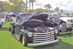 Oldie Pickup Trucks. These two old pickup trucks from different bygone eras are on display at a car show. Note that trucks had grown in size from the 1930`s era Stock Photo
