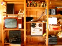 Oldies in the attic. Old technology and music in a sun lit attic. TV, tape recorders, tapes, old radio, books royalty free stock image