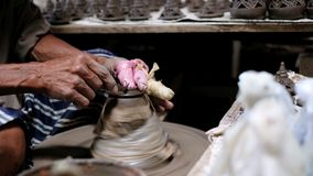 Oldman shaving the clay pot lid for perfect shape. In his factory stock footage