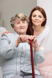 Oldness doesn't have to be sad time. Senior with walking stick and young women embracing her Stock Images