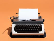 Oldschool typewriter with a blank page. On an orange background. Writer concept Stock Images