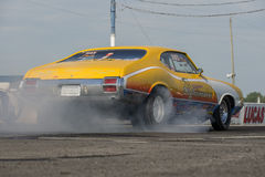 Drag racing. Napierville dragway, canada - july 12, 2014 rear side view of Oldsmobile cutlass during burnout at starting line during nhra national open event Stock Image