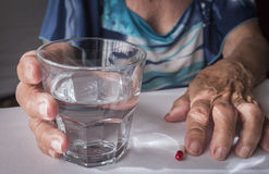Oldster taking daily medication dose at home. Andalusia, Spain Royalty Free Stock Image