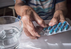 Oldster taking daily medication dose at home. Andalusia, Spain Stock Photography