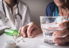 Oldster taking daily medication dose at home stock photography
