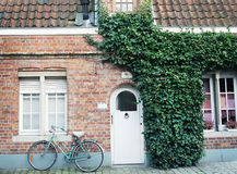Oldstyle bicycle in front of the red brick wall Stock Images