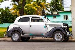 Oldtimer americano de Cuba debajo de las palmas Foto de archivo libre de regalías