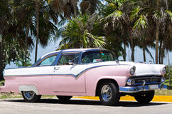 Oldtimer blanco americano de Cuba parqueado debajo de las palmas Imagen de archivo