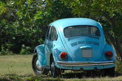 Oldtimer blue car. A little blue oldtimer car (VW Volkswagen beetle) parked in the shade during summer in the park outdoors stock photo