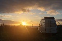 Oldtimer campervan parkeren bij de oceaan terwijl de zon plaatst royalty-vrije stock foto's