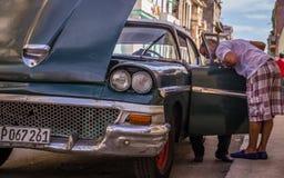 Oldtimer cubano de la fijación del mecánico después de la avería fotos de archivo