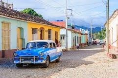 Oldtimer davanti alle case variopinte in Trinidad, Cuba Immagine Stock Libera da Diritti