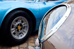 Oldtimer detail. View on front light of a brown classic roadster with a blue classic sports car in background royalty free stock images