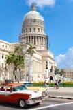 Oldtimer in im Stadtzentrum gelegenem Havana mit dem ikonenhaften Kapitolgebäude Stockbilder