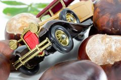 Vintage toy car surrounded by conkers in autumn composition royalty free stock images