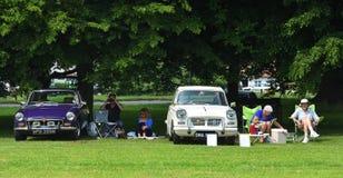 Oldtimer und Inhaber, die ein Picknick auf dem Dorfanger haben Truimph-Verkünder-und MG-Automobile Stockfotografie