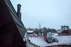 Oldtown Roofs During the Fog and Drizzle in Tallinn. Oldtown roofs in Tallinn, Estonia. The fog, drizzle and partially visible church tower in the background Stock Images