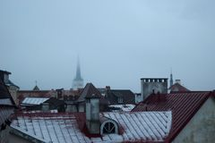 Oldtown Roofs During the Fog and Drizzle in Tallinn. Oldtown roofs in Tallinn, Estonia. The fog, drizzle and partially visible church tower in the background Royalty Free Stock Photography