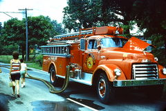The Ole Fire Engine. Est 1965 a fire truck on the side road suppling water and hose Royalty Free Stock Photos