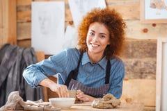 Oleiro alegre da mulher que senta-se e que trabalha no estúdio da cerâmica da arte imagem de stock