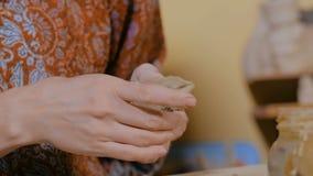 Oleiro da mulher que faz a moeda de um centavo cerâmica da lembrança assobiar na oficina da cerâmica video estoque