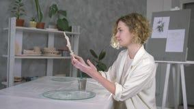 Oleiro da profissão, desenho fêmea do artesão talentoso através da escova na placa recentemente terminada do oleiro no estúdio do filme
