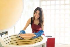 Oleiro de sorriso que coloca a oficina de Clay Dish Into Kiln At imagem de stock