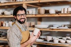 oleiro de sorriso que guarda o copo cerâmico na oficina com dishware imagens de stock royalty free