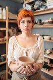 Oleiro fêmea que guarda a bacia da argila no estúdio imagem de stock royalty free