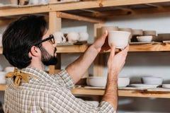 oleiro masculino com o dishware cerâmico em prateleiras na oficina fotografia de stock