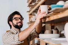 oleiro masculino de sorriso que trabalha com o dishware cerâmico em prateleiras fotografia de stock royalty free