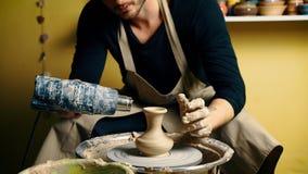 Oleiro masculino profissional que seca o potenciômetro cerâmico com o secador especial na oficina da cerâmica vídeos de arquivo