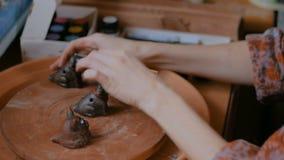 Oleiro profissional que pinta o assobio cerâmico da moeda de um centavo da lembrança na oficina da cerâmica filme