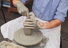 Oleiro que dá forma à argila em uma roda de oleiro Imagens de Stock
