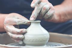 oleiro que faz o potenciômetro cerâmico na roda da cerâmica imagem de stock