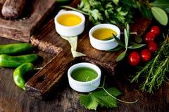 Oleje, pikantności ahd ziele wybór Winogrona, oliwki i kukurydzanych olejów świezi ziele, cytryny pieprzą CSelective ostrość Zdjęcia Royalty Free