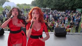 Concert outdoors, two girls in red dresses sing into microphone at the camera on the background of a crowd of people. Oleshky, Ukraine 1 October 2017: concert stock video