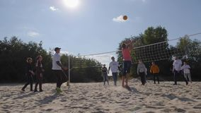 Young friends playing volleyball at the playground on background green trees and blue sky in backlight. Oleshky, Ukraine 1 October 2017: young friends playing stock video footage