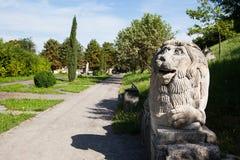 Olesko, Ucrânia - 23 de julho de 2009: Figura rachada rochoso do leão na entrada ao castelo Ucrânia de Olesko, região de Lvivska, Fotografia de Stock Royalty Free
