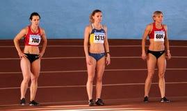 Olesya Povh and Mariya Rymyen. (L-R) Olesya Povh, Piatochenko Viktoria and Mariya Ryemyen on the start of 60 meters dash on the Ukrainian Cup in Athletics, on Stock Photography