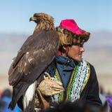 OLGIY, MONGÓLIA - 30 DE SETEMBRO DE 2017: Cazaque Eagle Hunter dourado na roupa tradicional, com uma águia dourada em seu braço Imagem de Stock Royalty Free