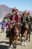 Mongolian Kazakh Eagle Hunter traditional clothing, holding a golden eagle on his arm Royalty Free Stock Image